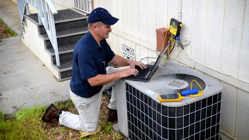contractor using a laptop to perform air conditioning service
